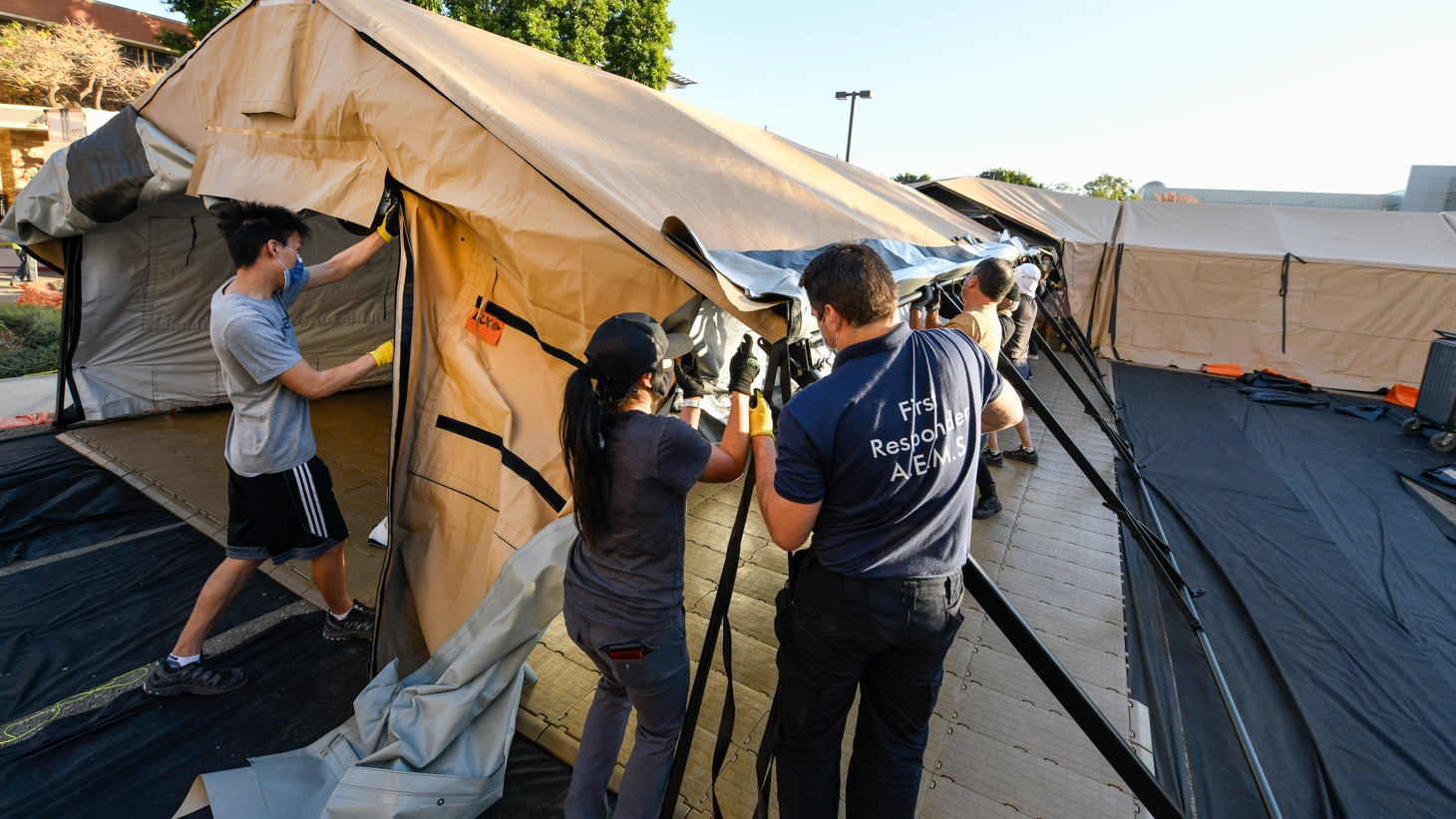 Volunteers work on assembling temporary buildings next to the emergency room entrance at University of California, Irvine Medical Center. Hospital officials say the buildings will be used to help ease the strain on their emergency room during the coronavirus pandemic. December 21, 2020.