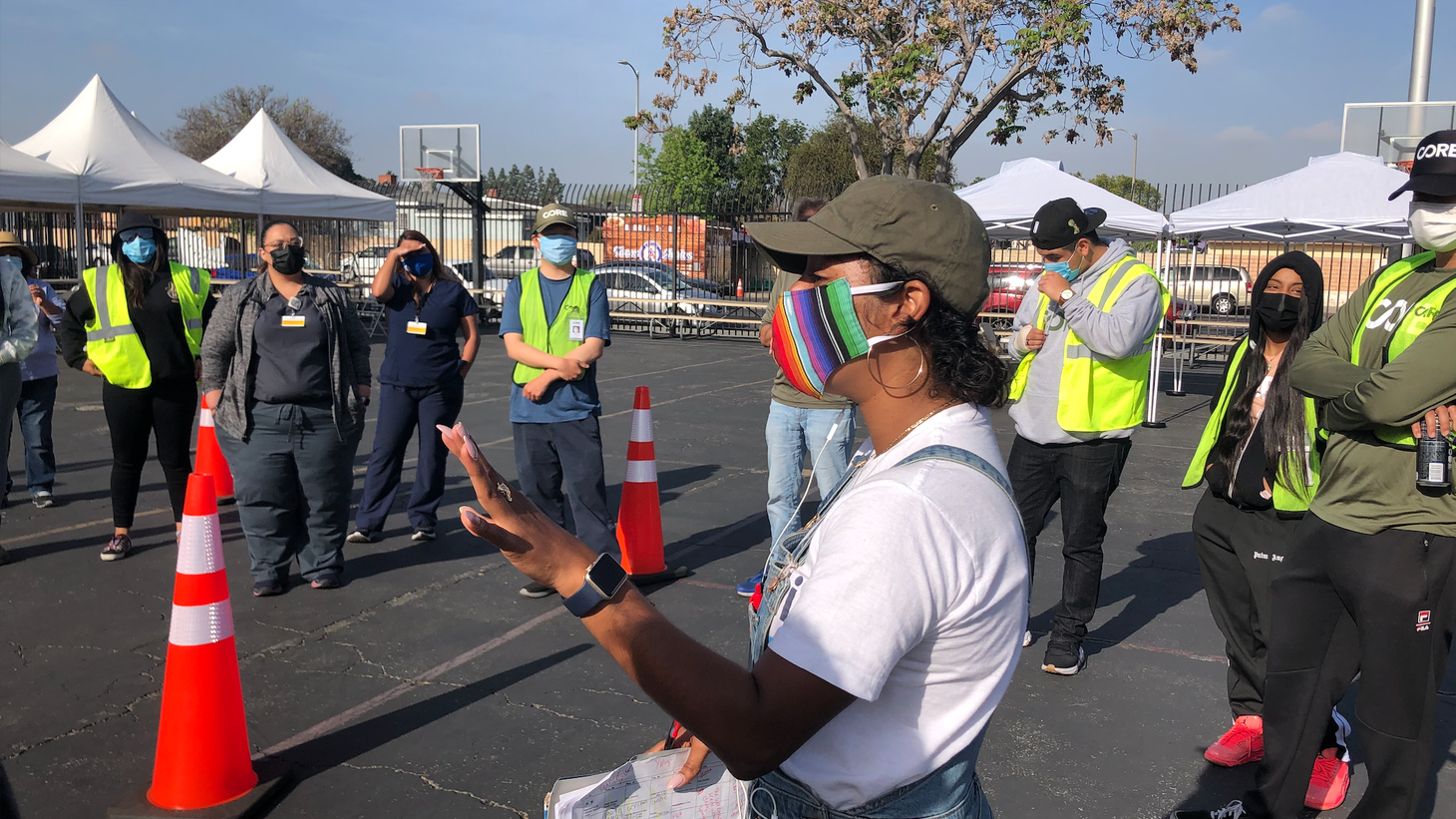 Johanna Rodriguez rallies workers in a morning huddle before the first patients walk into the mobile vaccination site at Watts.
