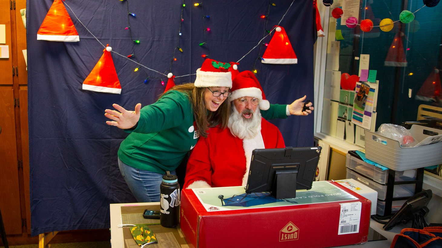 Santa Claus, right, and Mrs. Claus, aka Corey and Holly Anderson, participate in a Zoom video from Santa's makeshift office-turned-studio at the Eugene Family YMCA.