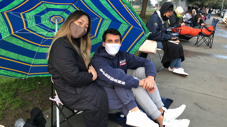 Many Angelenos are camping out on a sidewalk overnight to be first in a daily unofficial standby line for leftover COVID-19 vaccine doses.