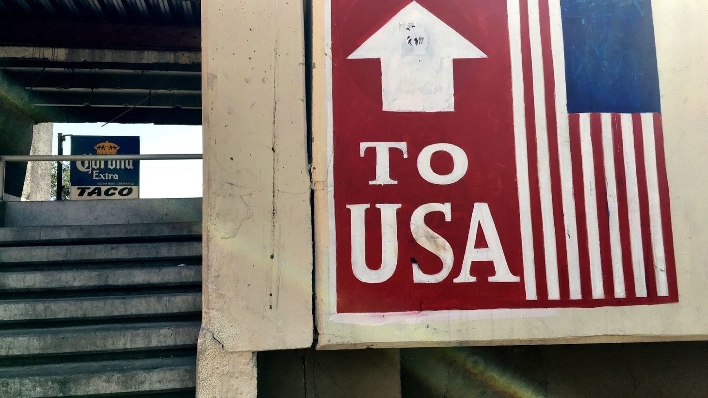 A sign at the pedestrian bridge over the Tijuana River heading to the US border crossing.