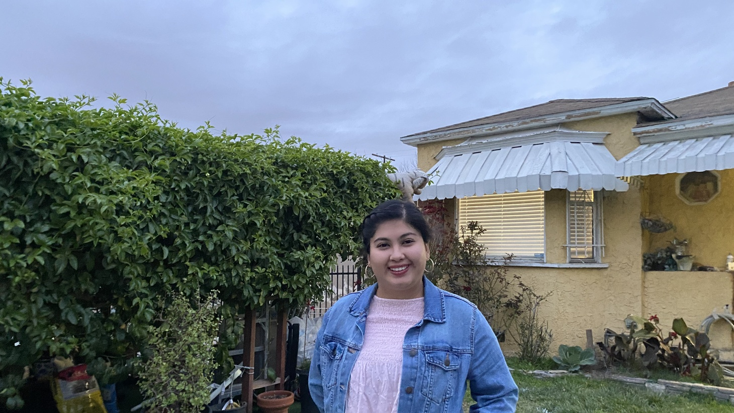 Andrea Galdamez, 21, in front of the home she shares in South LA with three generations of her family. COVID-19 recently sickened the entire family.