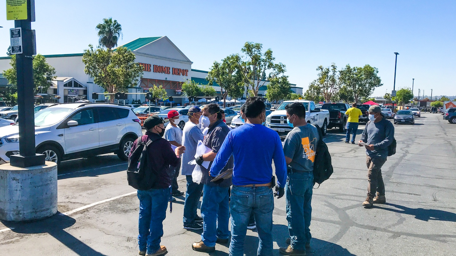 Day laborers crowd around activists who distribute masks, hand sanitizer and literature about COVID-19 at a Home Depot in Alhambra.
