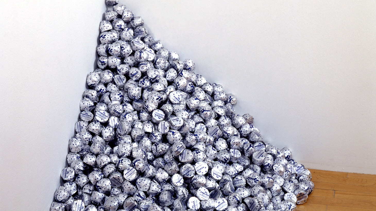 """Felix Gonzalez-Torres, """"Untitled"""" (A Corner of Baci), 1990, endless  supply of Baci chocolates individually wrapped in silver foil, ideal  weight: 42 lbs., dimensions variable. The Museum of Contemporary  Art, Los Angeles, purchased with funds provided by the Ruth and  Jake Bloom Young Artist Fund."""
