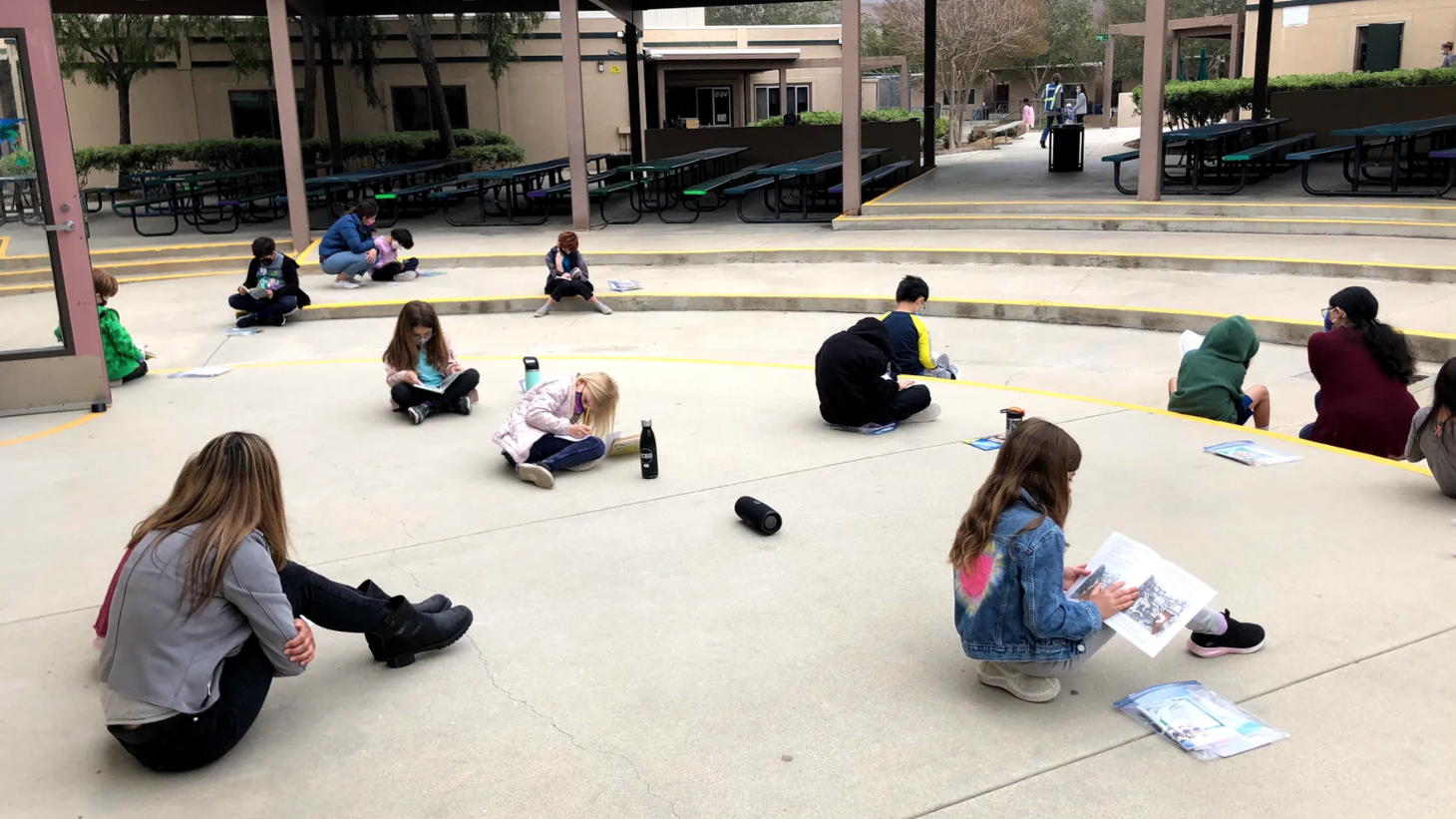 Students at Red Oak Elementary sit socially distanced and masked during outdoor reading time.