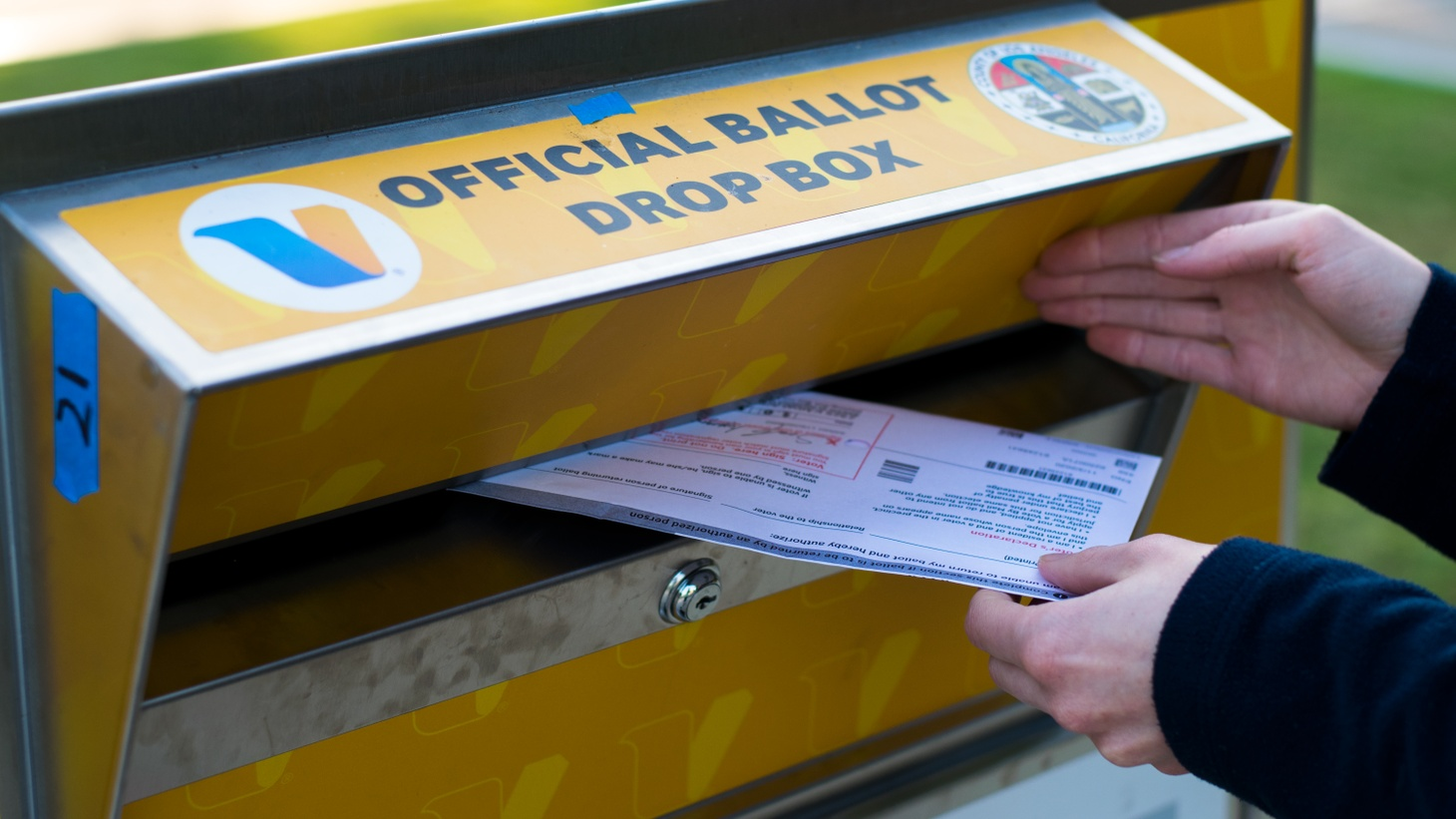 A Los Angeles resident submits their mail-in ballot to an official drop box in Santa Monica, Oct 11, 2020.