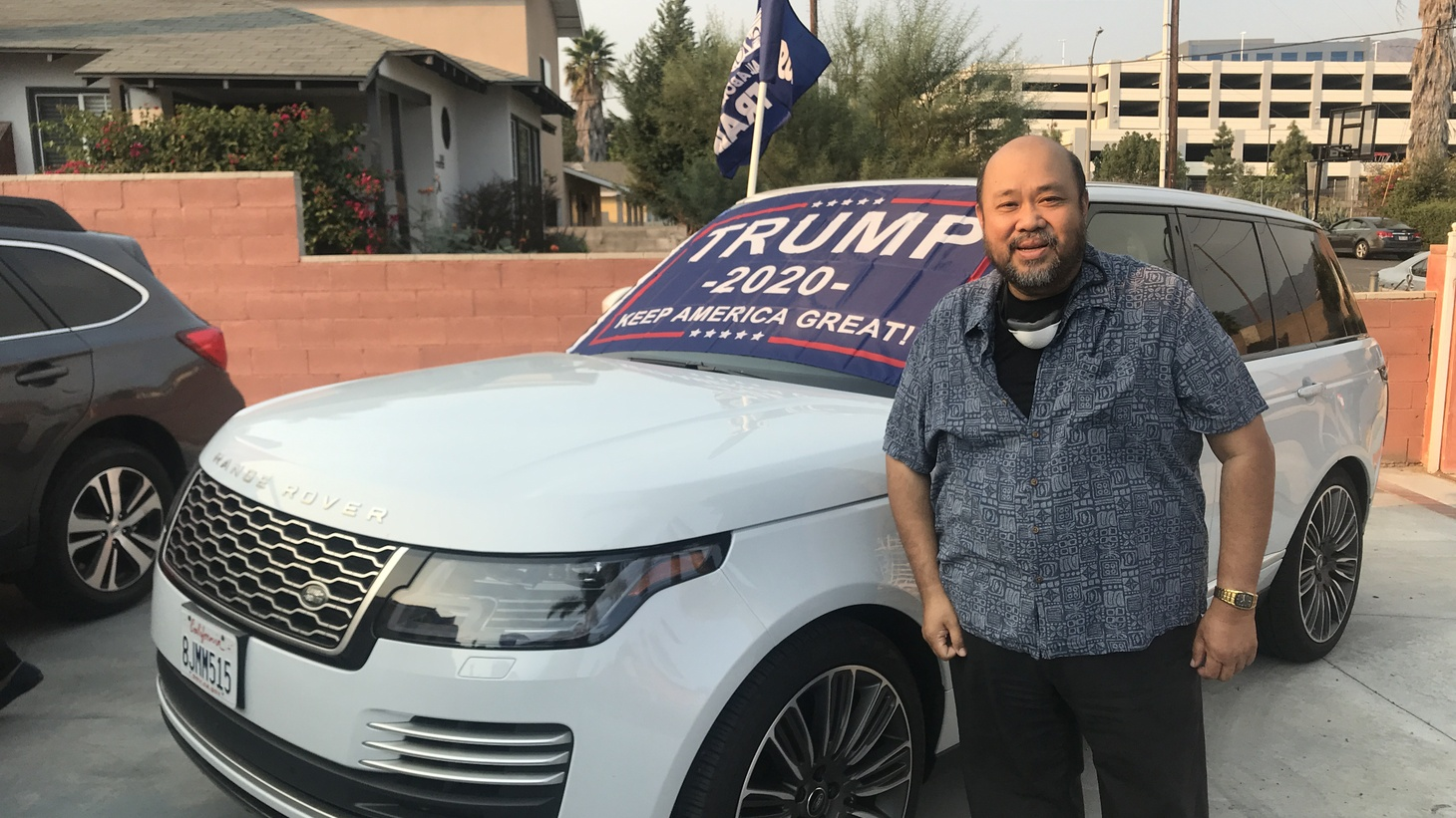 Noel Omega, a Filipino American and Trump supporter, stands outside one of the cars being decorated ahead of a weekend rally.