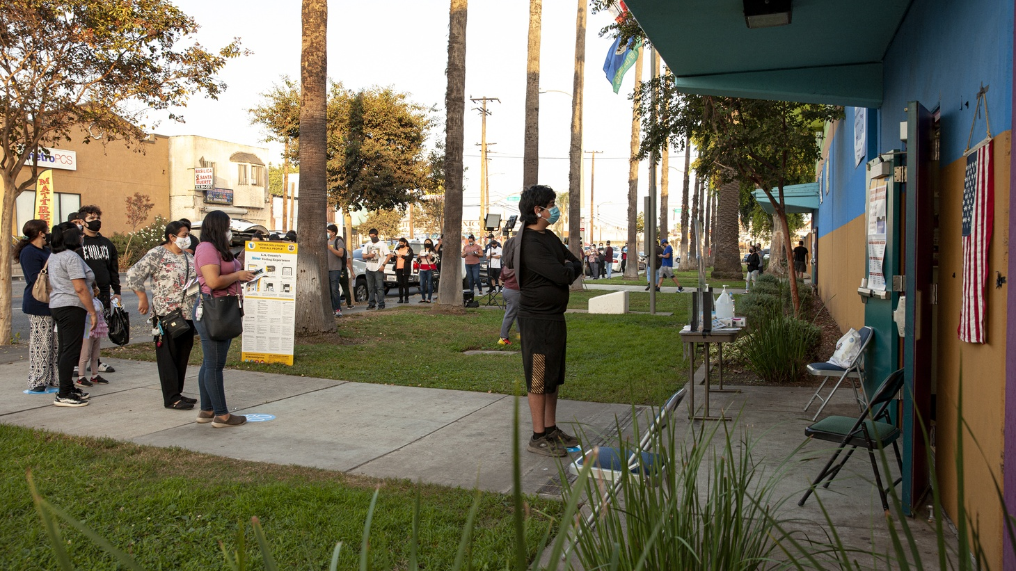 People wait in line to vote at Ruben Salazar Park as the sun sets.