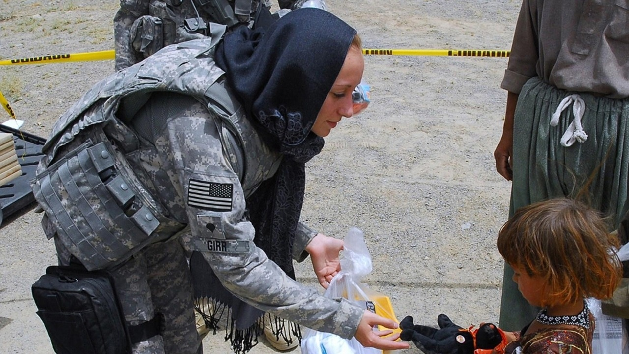 A female soldier giving a toy to a child.
