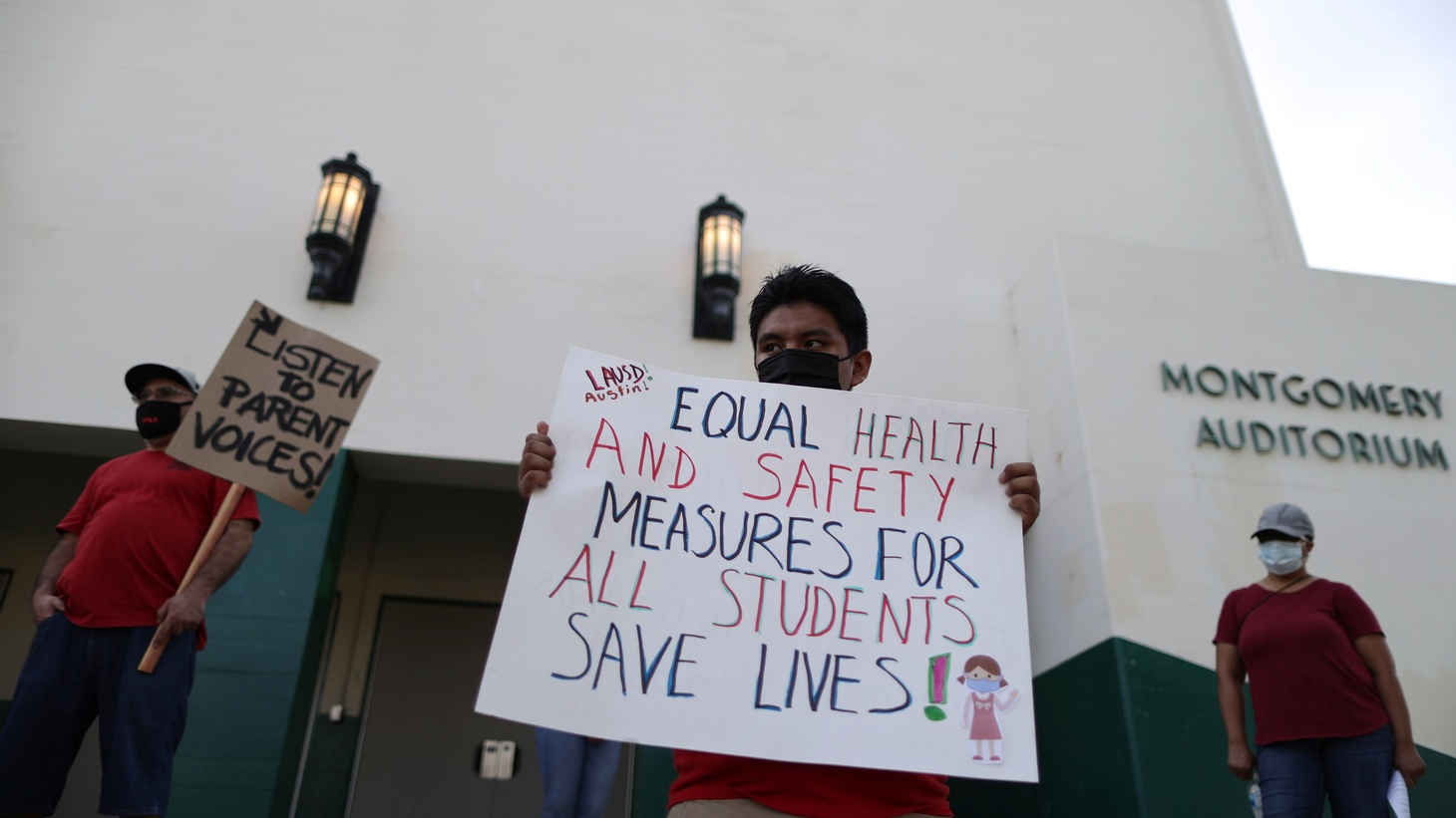 People hold signs at a protest for parents, students, and educators outside Dorsey High School to urge LAUSD not to reopen schools without strong COVID safety measures, during the coronavirus disease outbreak, in Los Angeles, California, U.S., October 15, 2020.