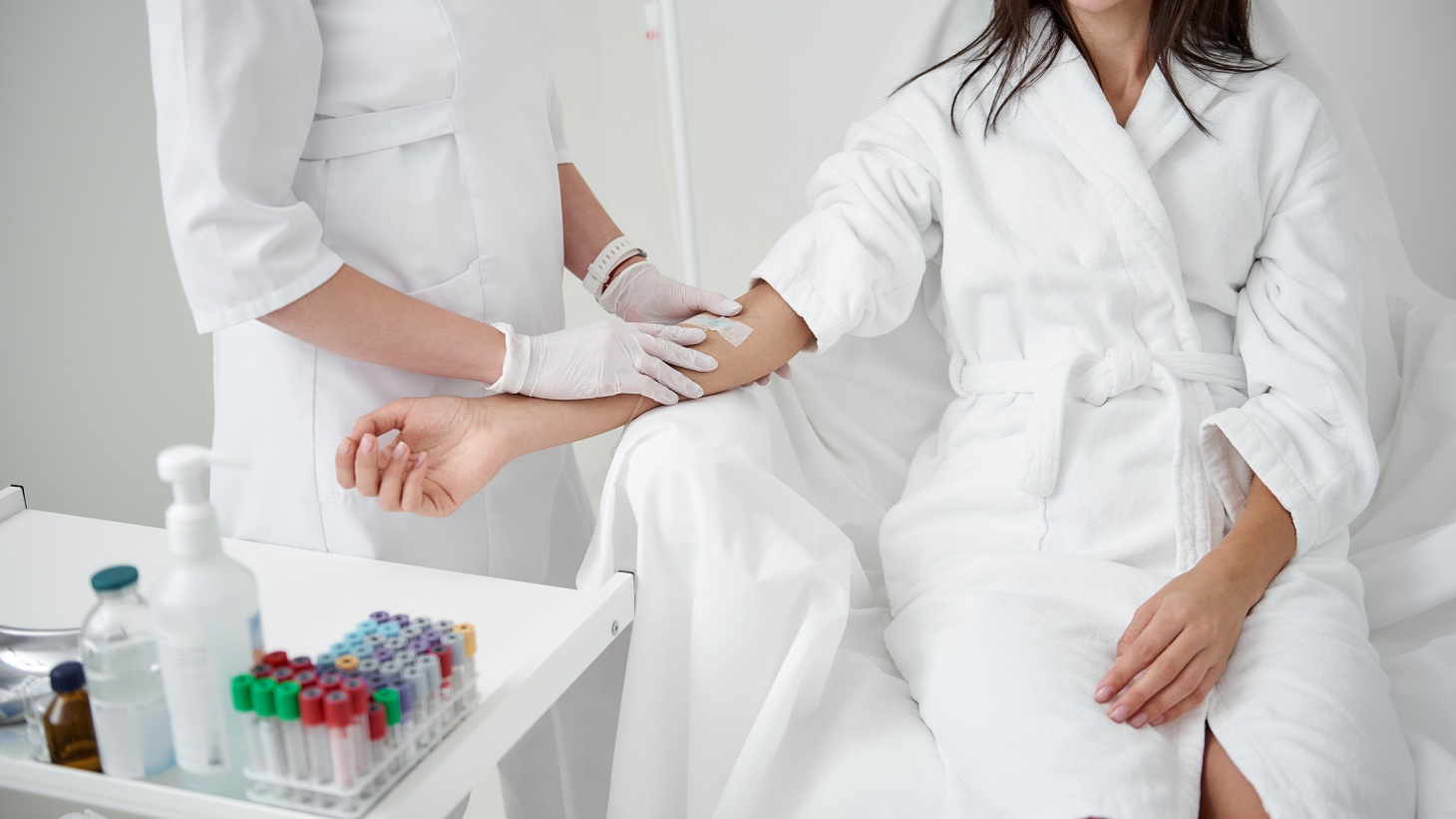 """A health care provider prepares a client for an IV infusion — a procedure offered at some """"concierge medicine"""" practices."""