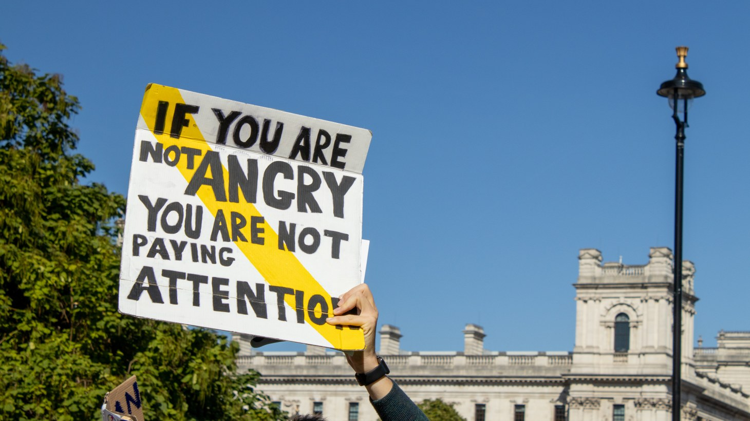 """At a climate rally in London, an activist holds a sign that says, """"If you are not angry, you are not paying attention."""""""