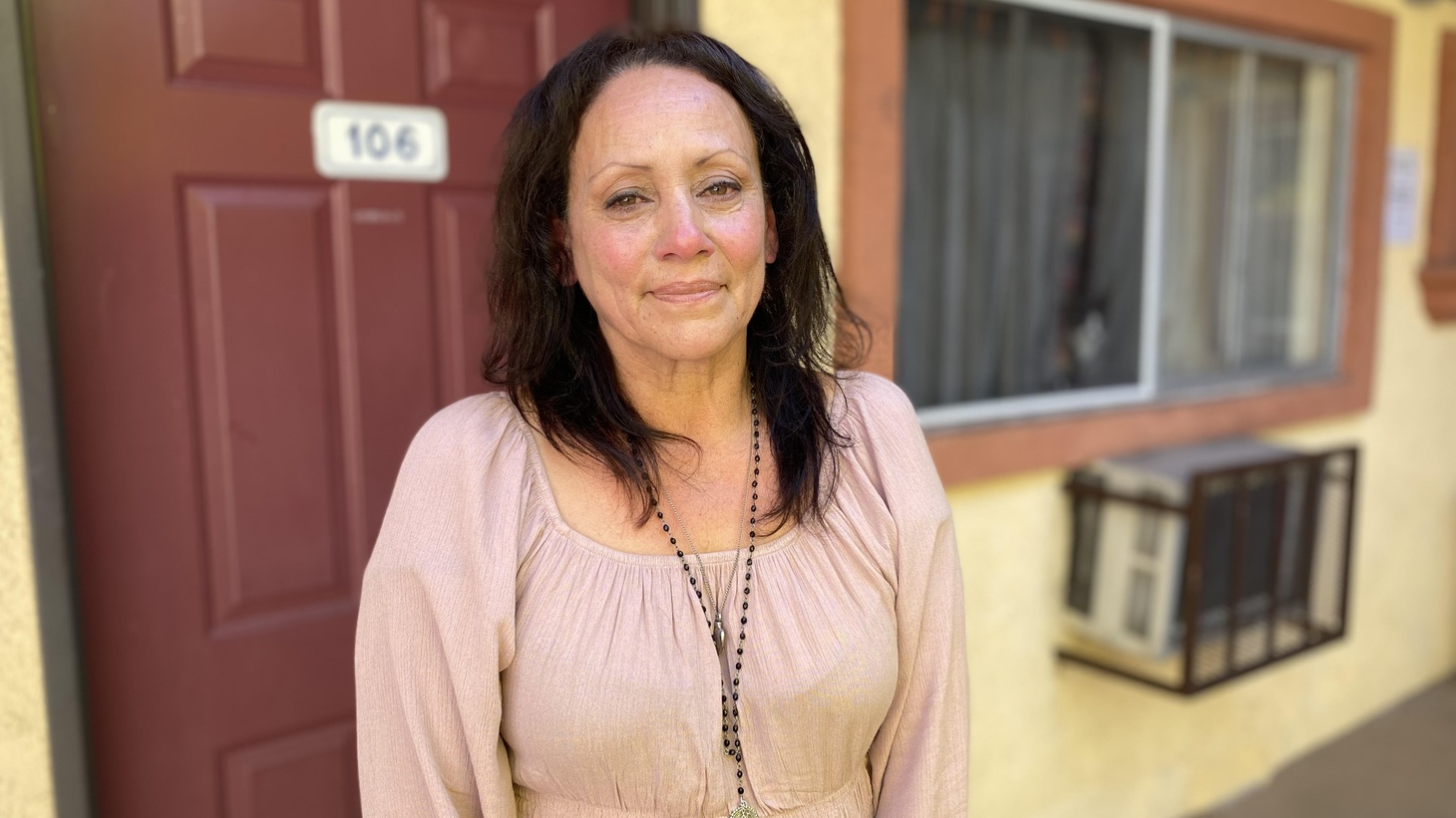 Veronica Marmion stands outside her Project Homekey room in LA's Adams District.