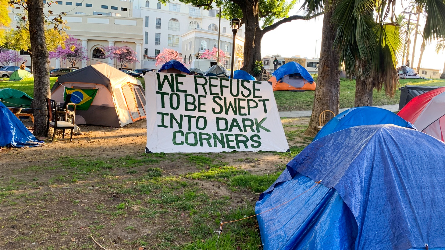"""A sign by homeless camps at Echo Park Lake says, """"We refuse to be swept into dark corners."""" March 24, 2021."""