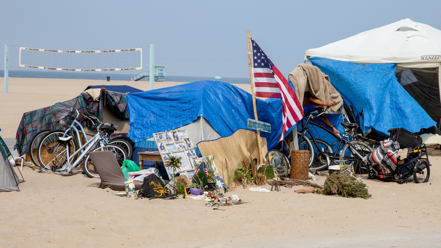 """Along the Venice boardwalk, an American flag with a sign reading """"home sweet home"""" is centered at the forefront of a homeless encampment. June 29, 2021. Photo by Zaydee Sanchez for KCRW."""