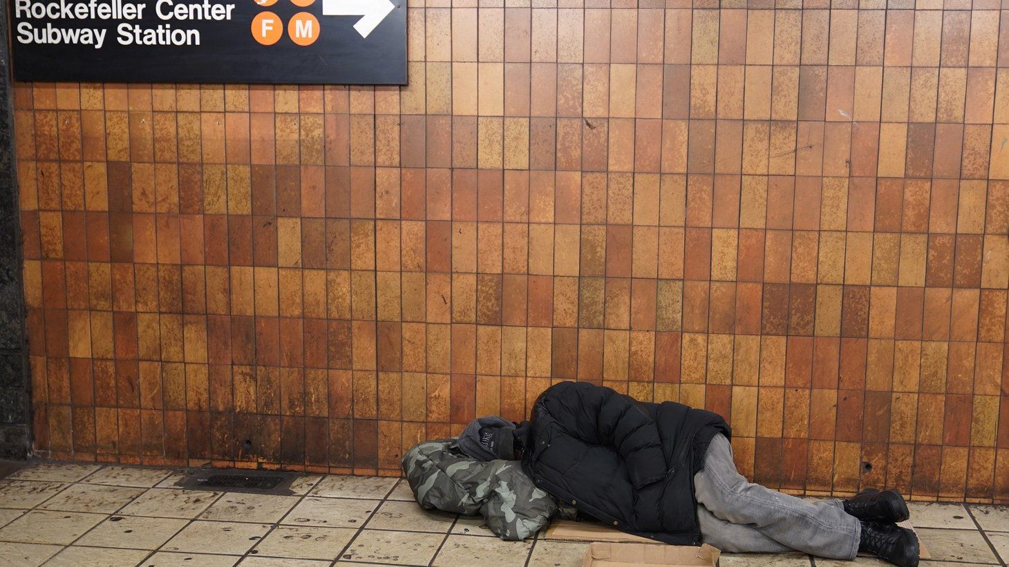 A person sleeps at Times Square subway station in Midtown Manhattan.