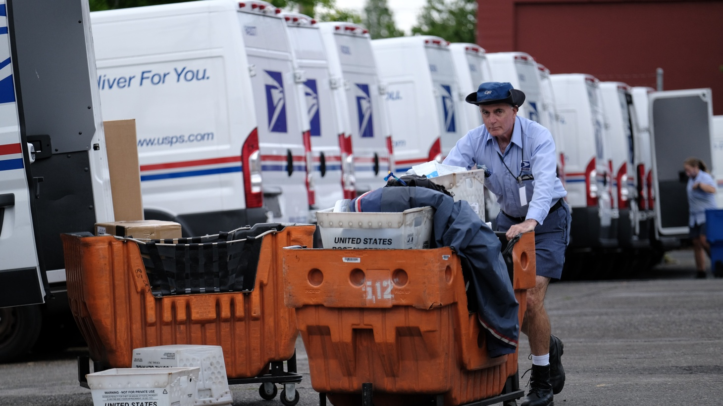 A postal worker loads mail into vehicles at the beginning of the day in Portland, Ore., on May 21, 2020, as cars circle the facility on Southeast 7th Avenue to show support for essential workers.