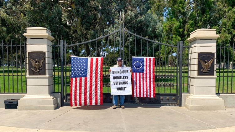 On San Vicente Boulevard in Brentwood, there's an unusual-looking homeless encampment. It's a row of nearly two dozen large, identical tents with American flags pinned to the outside.