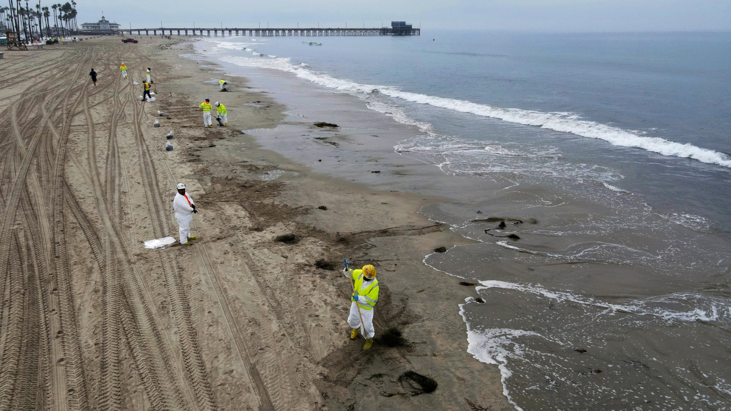 Workers rake up crude oil, after more than 3,000 barrels of crude oil leaked from a ruptured pipeline into the Pacific Ocean in Newport Beach, California, U.S., October 7, 2021. Picture taken with a drone.