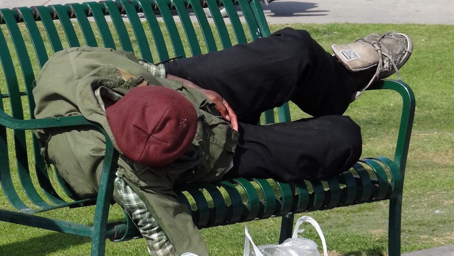 A homeless man naps on a bench in Santa Monica.