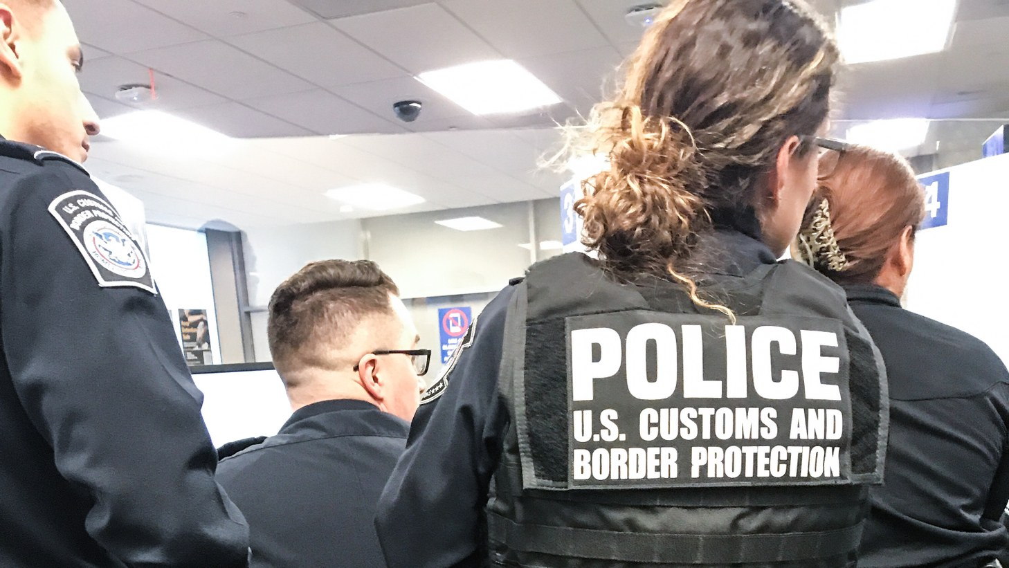 Members of the US Customs and Border Protection's Admissibility Review Unit at LAX huddle around a computer screen as they review a traveler's documentation.