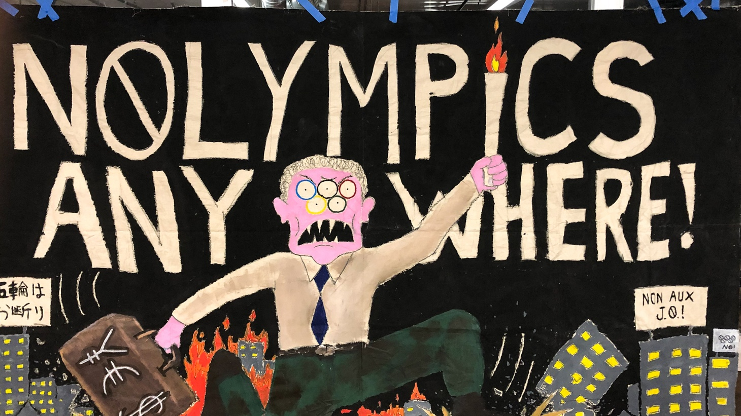 A poster hanging at the NOlympics meeting last month, where activists from Los Angeles and Tokyo talked about the families displaced by preparations for the Olympic games.