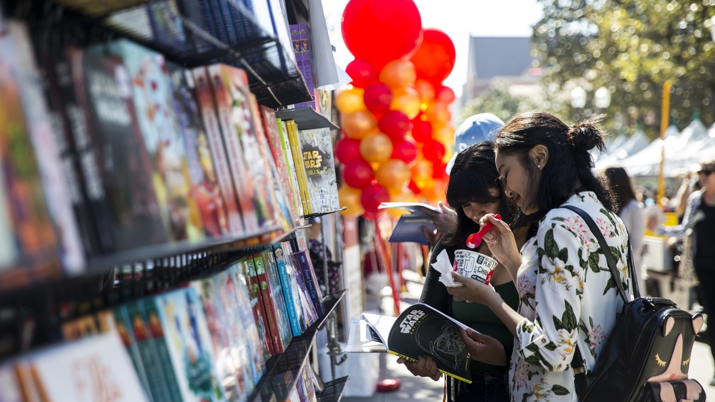Elisa Sifuentes, 16, and Kaitlyn Bin, 16, browse displays of books at the L.A. Times Festival of Books on the USC campus in 2018. This year's festival is going all online.