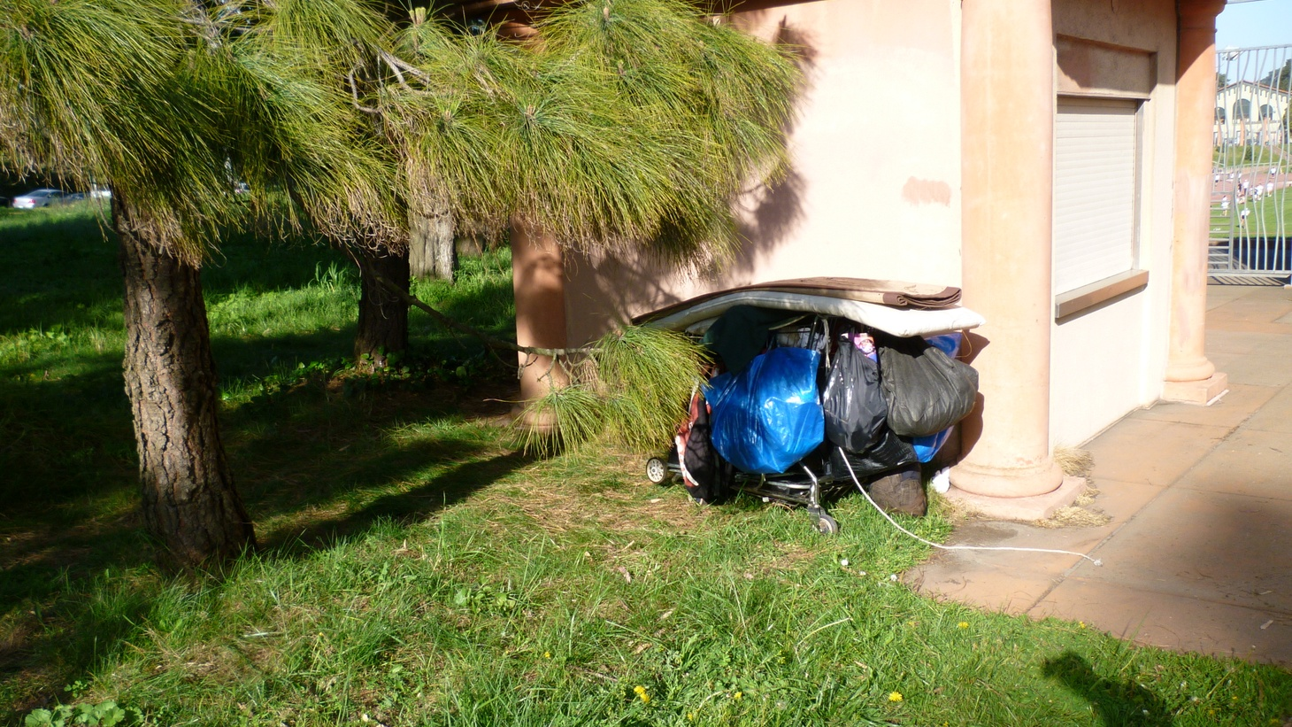 A shopping cart filled with belongings of an unsheltered person.
