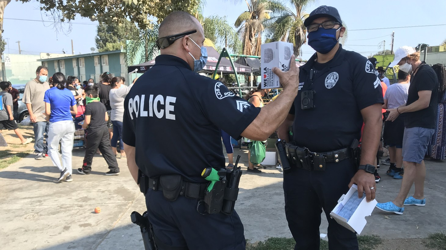 Two Community Safety Partnership officers stand watch as volunteers pass out school supplies at Watts Empowerment, a community center in the middle of the Imperial Courts housing project in Watts.