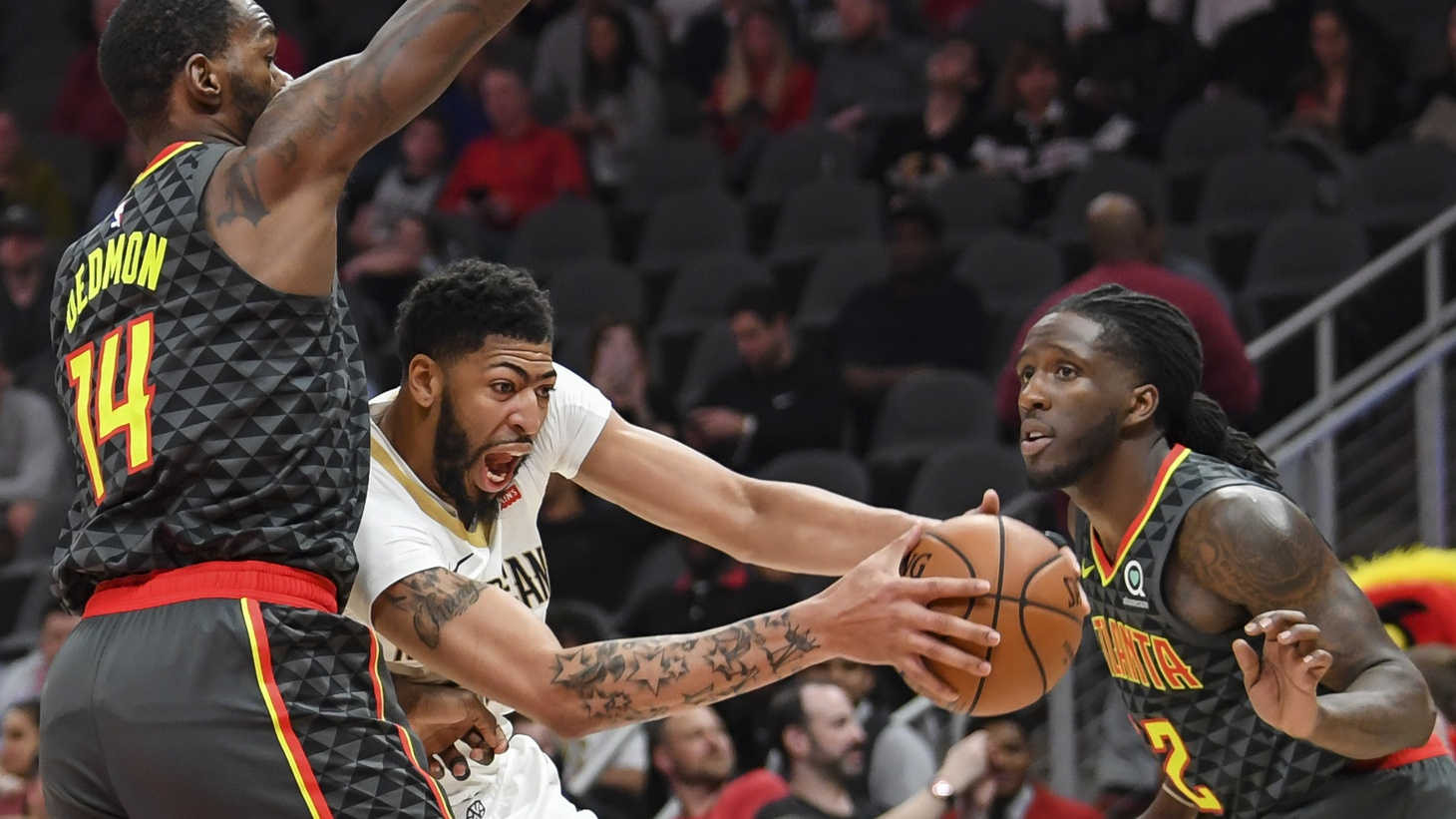 New Orleans Pelicans forward Anthony Davis (23) controls the ball between Atlanta Hawks center Dewayne Dedmon (14) and forward Taurean Prince (12) during the first half at State Farm Arena. Mar 10, 2019; Atlanta, GA, USA.