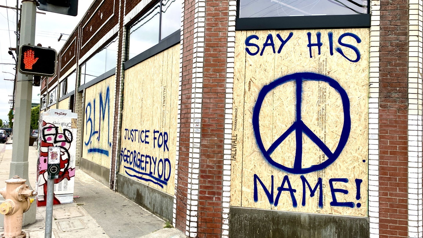 """Activists spray painted the words """"BLM,"""" """"Justice for #GeorgeFloyd,"""" and """"Say his name!"""" on a boarded-up business in Santa Monica. June 5, 2020."""