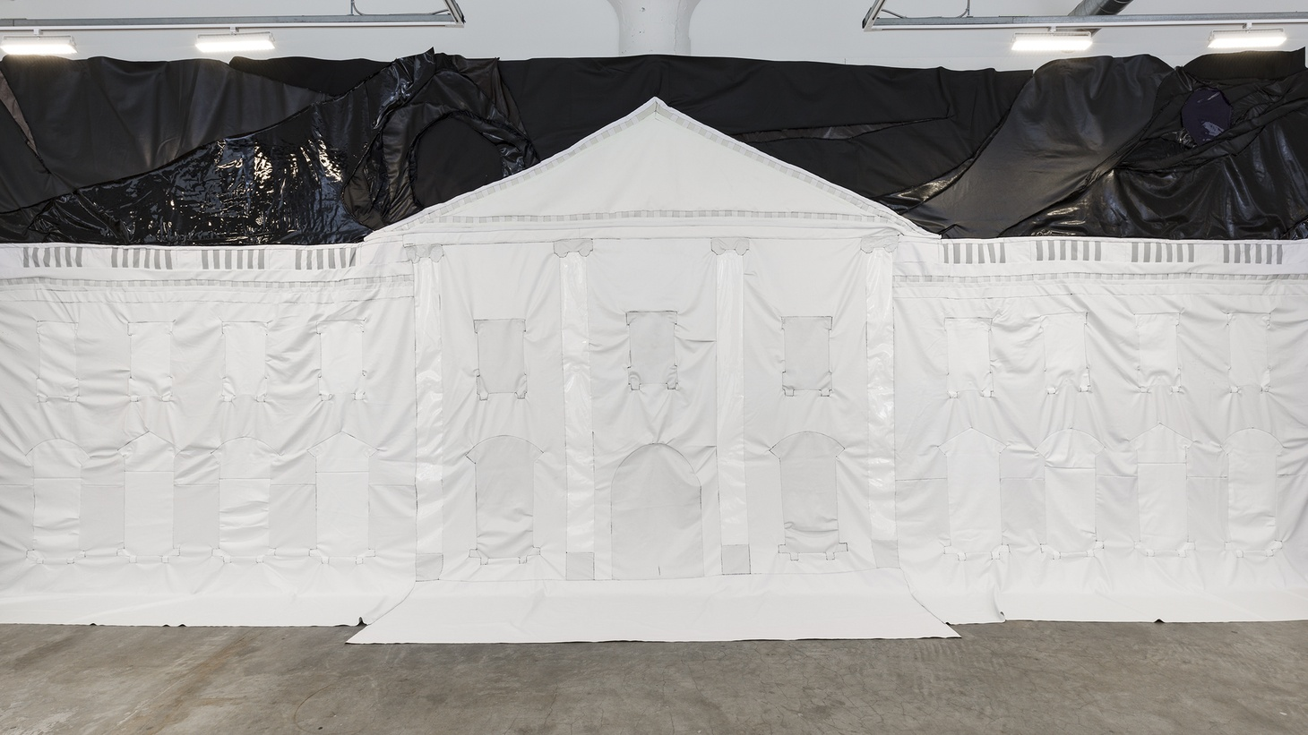 "Rodney McMillian's ""White House II"" is made out of fabric, so it needs the wall to support it, therefore undermining the symbolic strength of The White House with softness."
