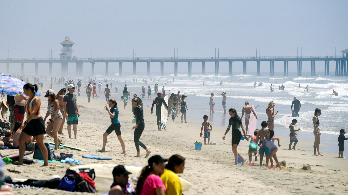 People walk up and down Huntington City Beach during the outbreak of the coronavirus disease (COVID-19), in Huntington Beach, California, U.S., April 25, 2020.