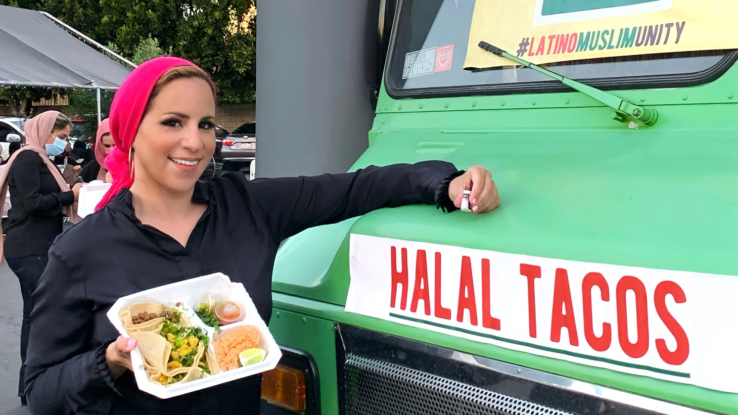 Rida Hamida holds a halal taco in one hand and a vaccination dose in the other at the Islamic Center of Santa Ana.