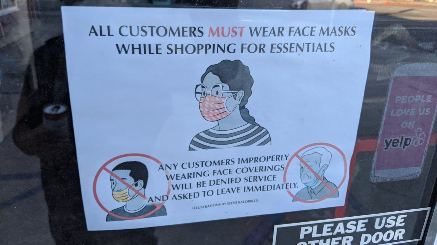 """A store in Burbank, California displays a sign that says, """"All customers must wear face masks while shopping for essentials. Any customers improperly wearing face coverings will be denied service and asked to leave immediately."""""""