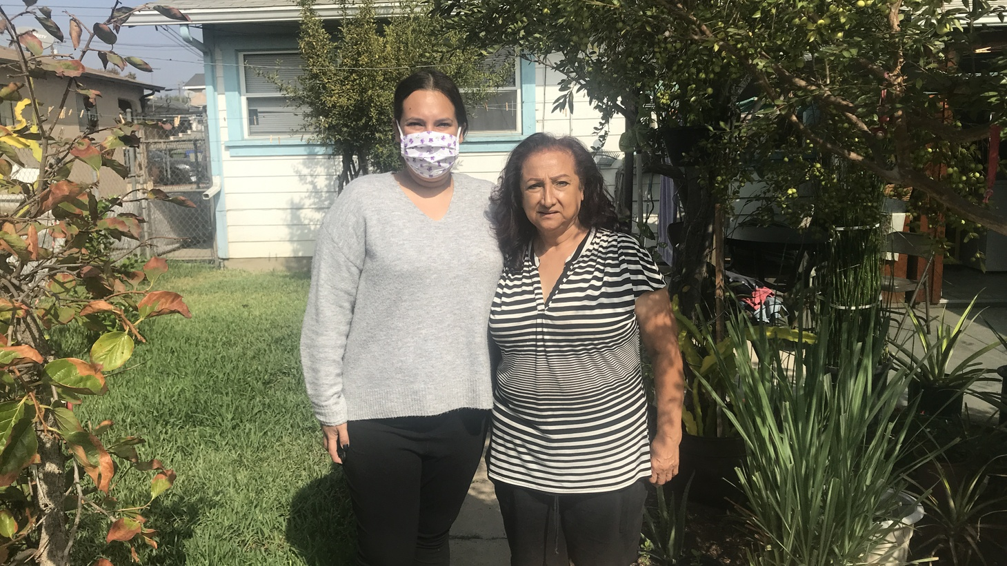 Guadalupe Valdovinos (left) and her mother Lourdes in their backyard in East Los Angeles. Their home is among hundreds that have been cleaned by the state due to elevated lead levels in the soil. However, Valdovinos still feels like she's in danger.