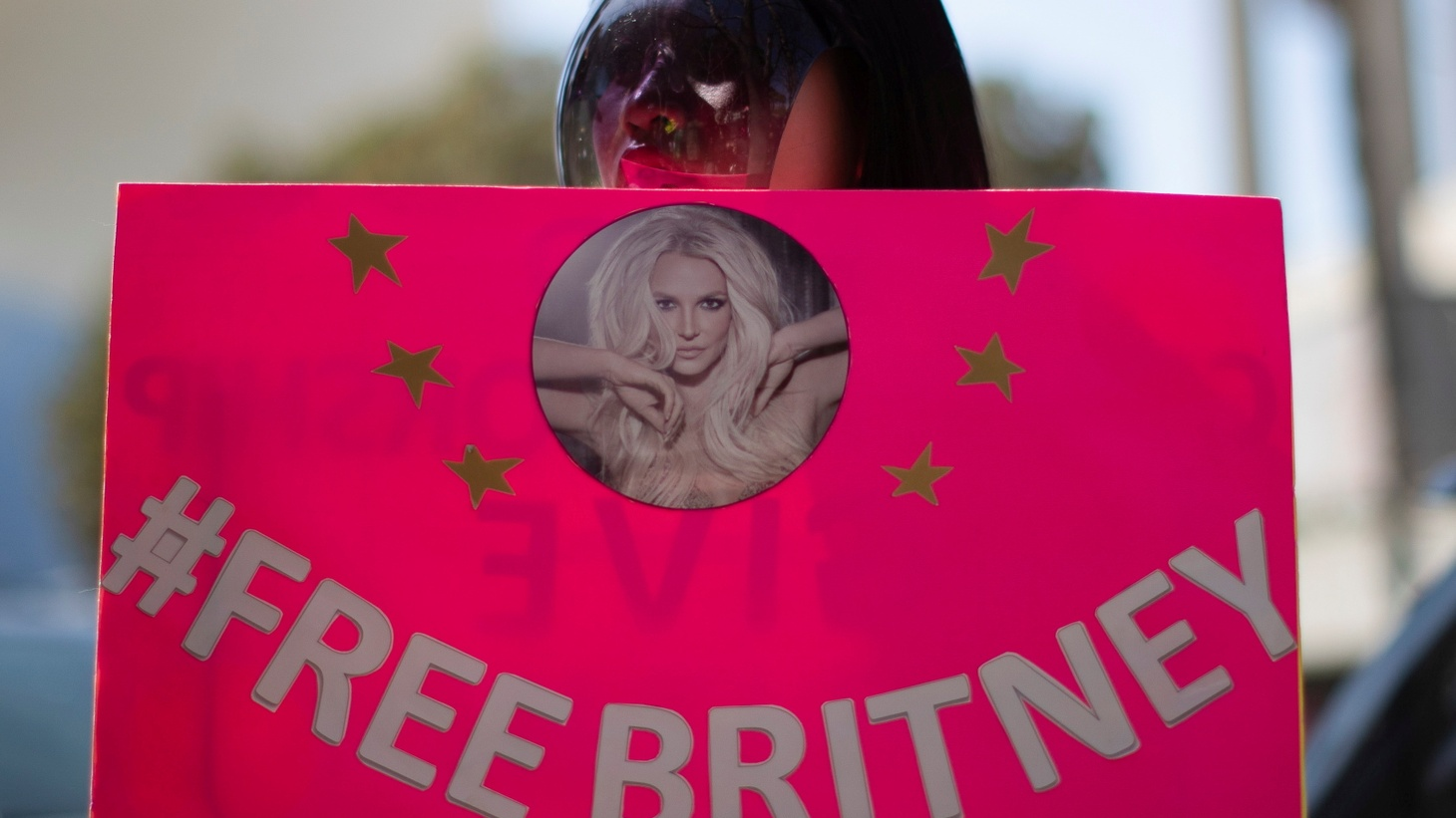 A supporter wearing a personal protective face shield holds a sign while rallying for pop star Britney Spears during a conservatorship case hearing at Stanley Mosk Courthouse in Los Angeles, California, U.S., March 17, 2021.