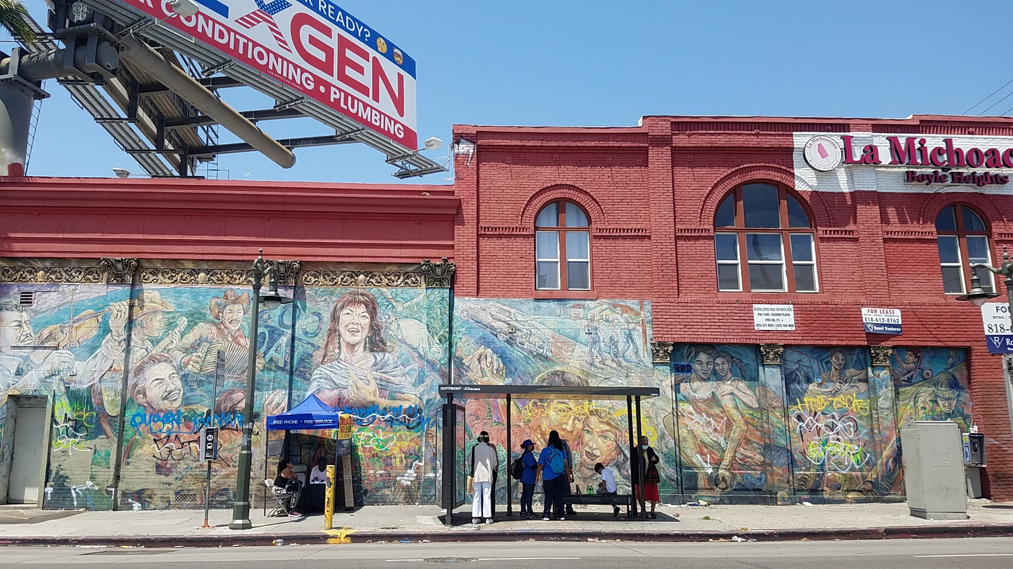 """A bus stop at Soto Street and Cesar Chavez Avenue is accented by the mural called """"Corrido de Boyle Heights."""""""