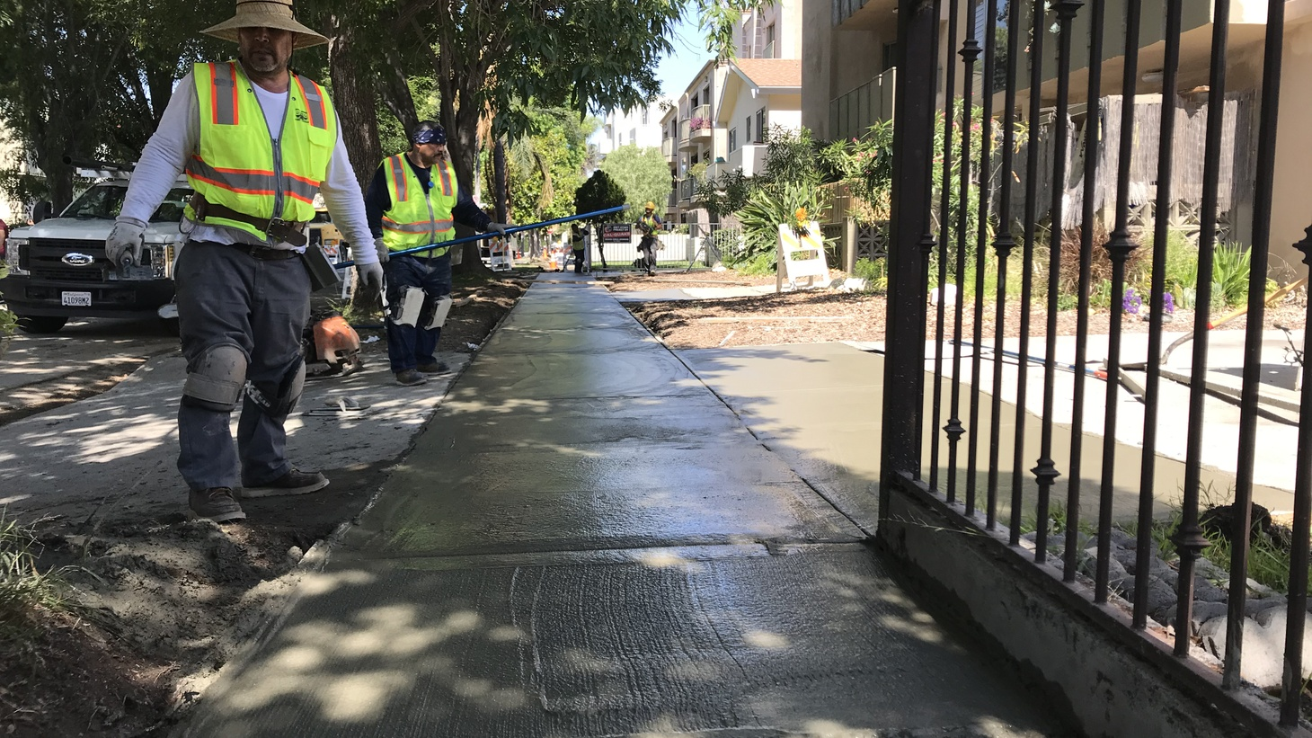 Construction crews contracted by the City of Los Angeles work to repair a stretch of sidewalk in the Pico-Robertson neighborhood of LA. The project is one of hundreds that the city is hoping to fix in the coming years.