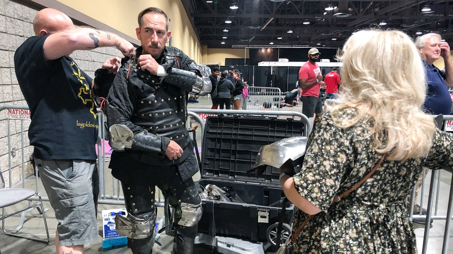 Brian Shirloff helps Marcus Kelley put on his armor before an afternoon of knight battles at the Long Beach Convention Center.