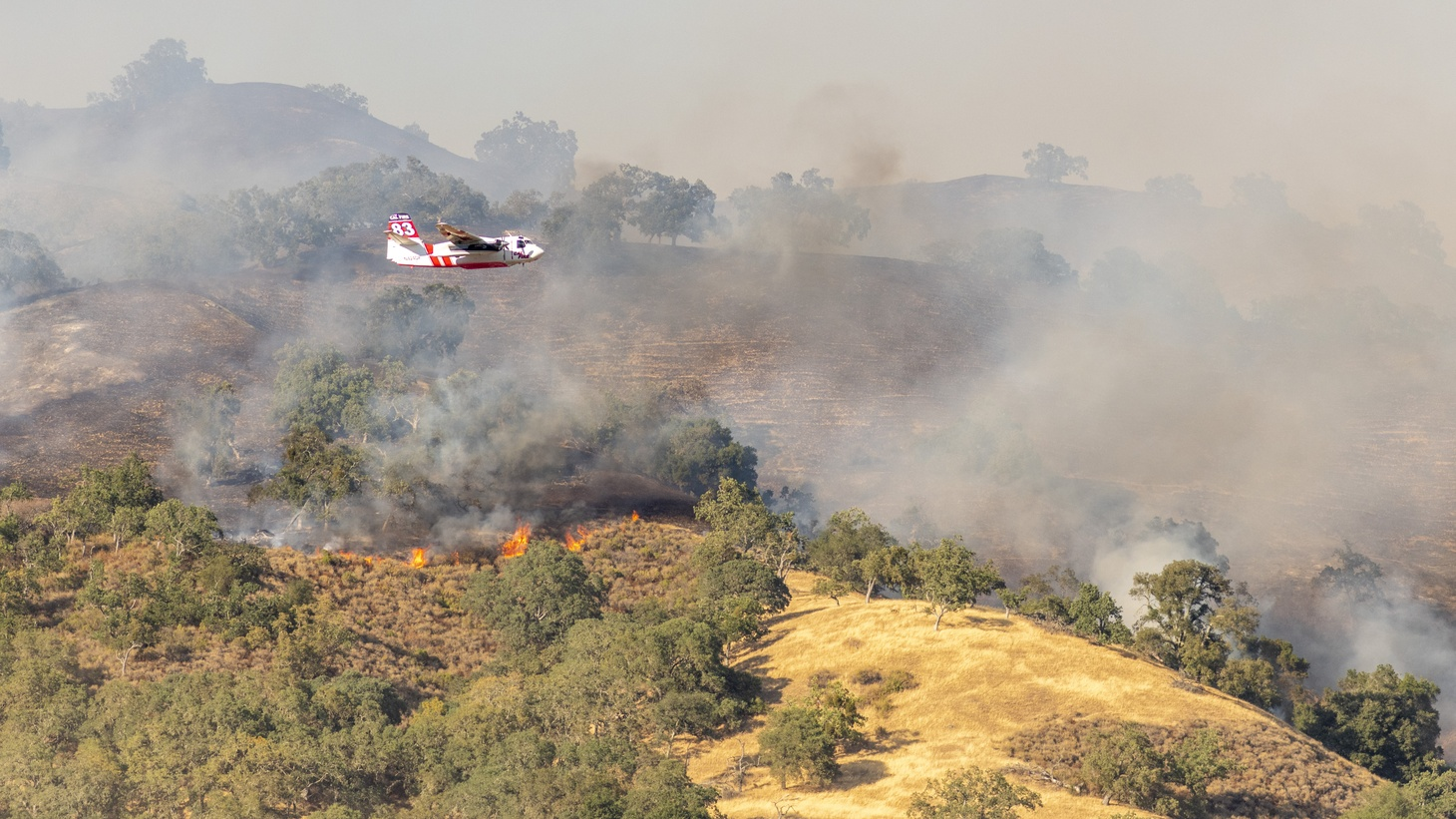 In an effort to control the spread of wildfire, a Cal Fire aircraft is spraying fire retardant on a hill in Santa Clara County, California, United States on August 20, 2020. Multiple large lightnings on Sunday, August 16, 2020, have caused fires burning in the mountains near Santa Clara and San Jose.