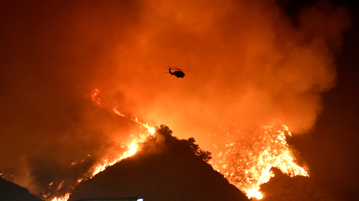 A firefighting helicopter flies over the Getty fire as it burns in the hills west of the 405 freeway in the hills of West Los Angeles, California, U.S. October 28, 2019.