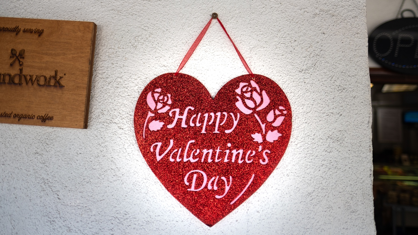 "A ""happy Valentine's Day"" sign hangs outside a business in downtown Culver City. Even during a pandemic and the age of social distancing, some people are still trying to find love, and some are successful."
