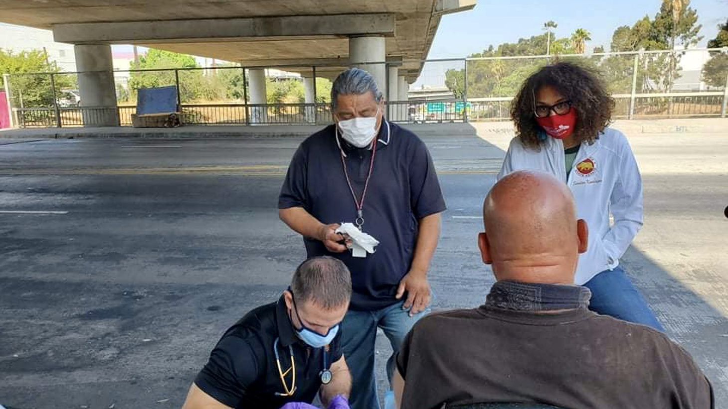 Physician assistant Brett Feldman treats a man who lives in a tent overlooking a freeway in downtown Los Angeles. Joseph Becerra, a community health worker, and State Senator Sydney Kamlager watch.