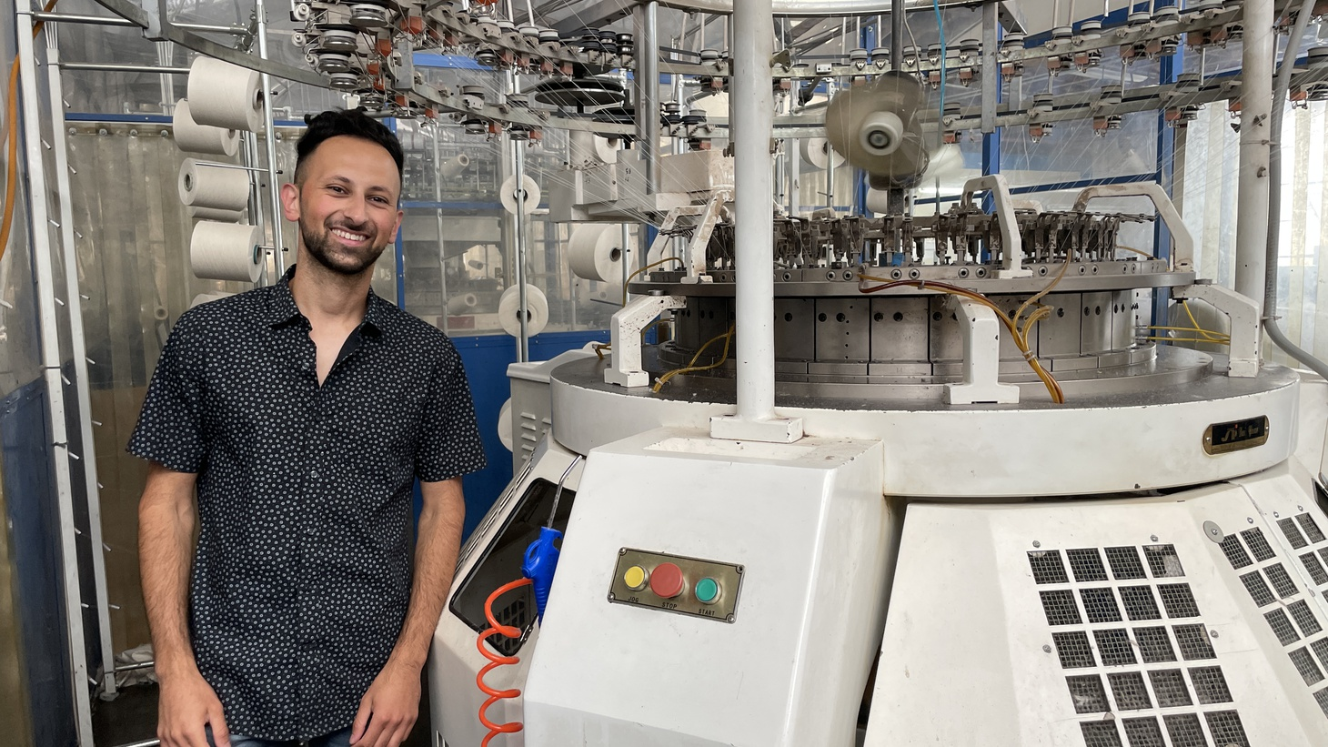 """Sean Zahedi stands next to one of his knitting machines at Lafayette Textiles in Vernon. """"My father used to have his own dye house. But because of rising labor costs, environmental regulations and water, it moved to Nicaragua,"""" he says."""