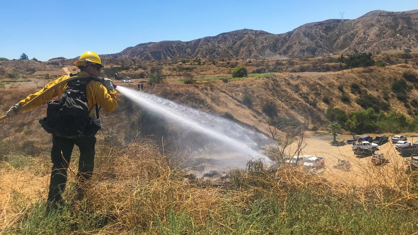 A firefighter with the U.S. Forest Service works to put out a brush fire in the Angeles National Forest