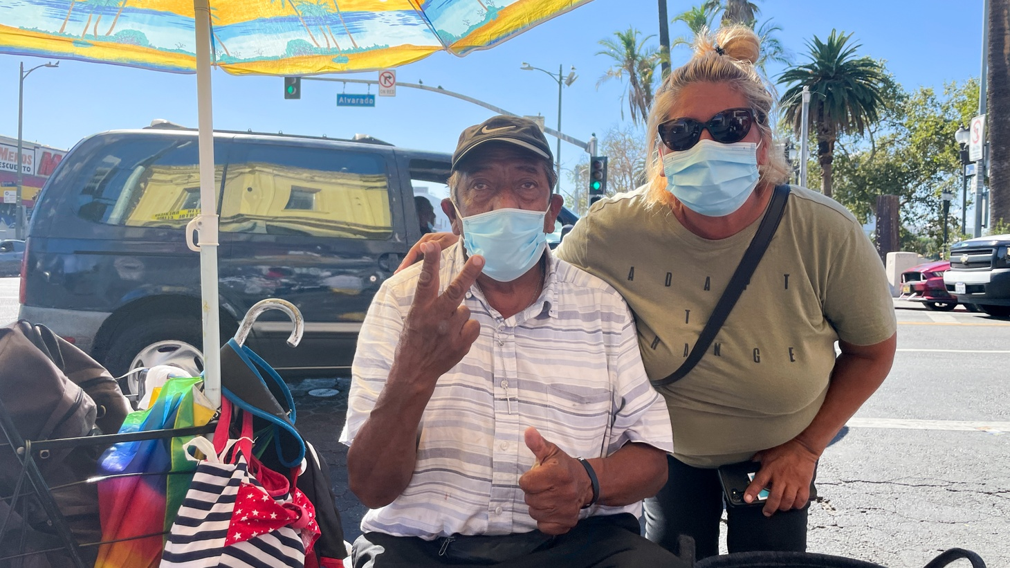 Elizabeth Medina (right) with her friend and street vending partner Victor Renteria pose for a photo as they sell electronics and other knick-knacks near MacArthur Park.