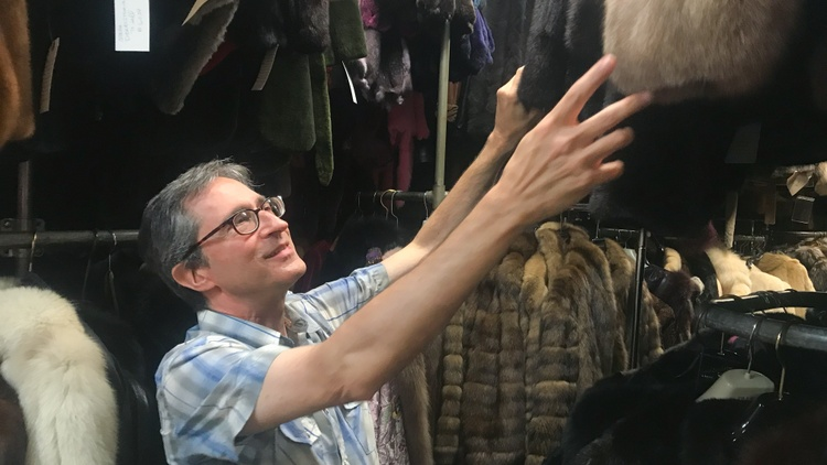 """Daniel Wachtenheim sifts through a rack of vibrantly-colored fur coats at his shop in downtown Los Angeles, listing off the animals they came from: """"This is sable."""