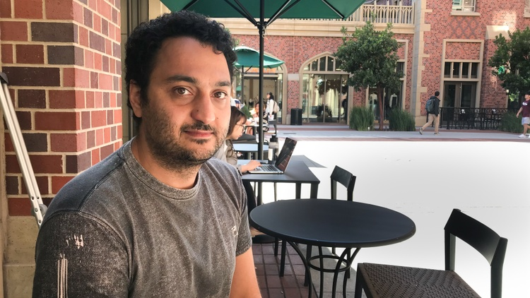 Sassan Yousefi walks gingerly along the red brick and concrete floors of the USC Village, a single crutch under his left arm.   