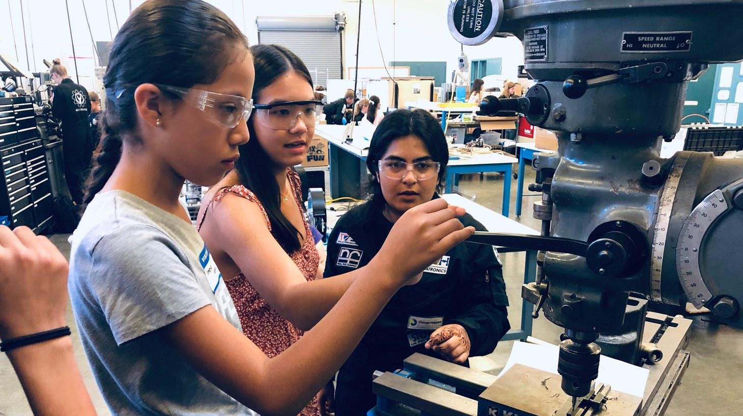 A Dos Pueblos Engineering Academy student helps guide visiting elementary students with a drill press.
